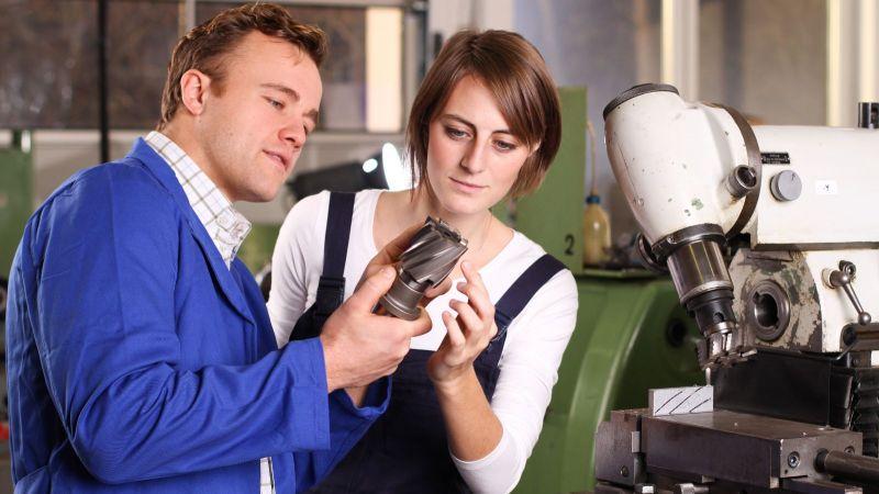 Frau und Mann begutachten Maschine